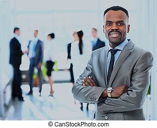 Portrait of a successful american african businessman smiling leading his team.