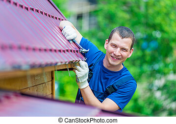 portrait of a successful experienced worker during roof repair