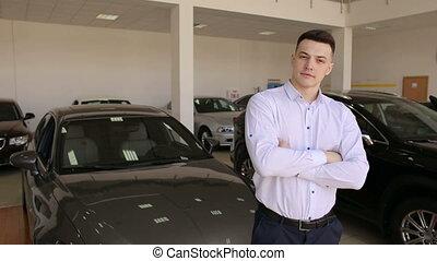 Portrait of a successful man in a white shirt in a modern car showroom.