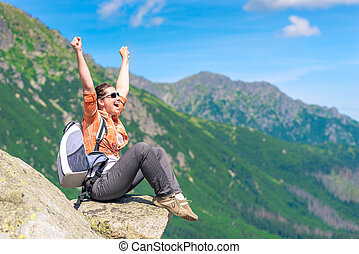 portrait of a successful tourist, sitting on the mountain and enjoying freedom