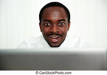 Portrait of a surprised african man in office
