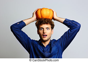 Portrait of a surprised man with pumpkin on head