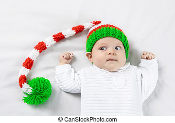 Portrait of a surprised three months old baby in elf's hat lying on the white blanket.