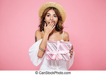 Portrait of a surprised young woman in straw hat holding present box, covering her mouth with hand