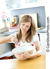 Portrait of a teen woman preparing a cake in the kitchen