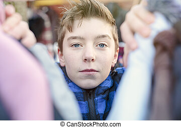 portrait of a teenage boy who is looking after clothes on a...