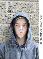 portrait of a teenage boy with grey hoodie sweatshirts standing in front of a wall.
