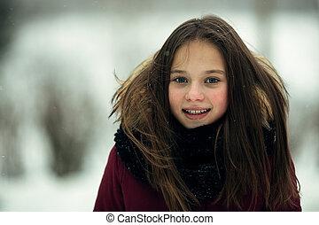 Portrait of a teenage girl outdoors in snowy winter.