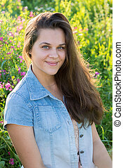 Portrait of a teenager 15 years with long hair in meadow