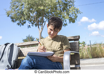 Portrait of a teenager boy sitting doing his homework