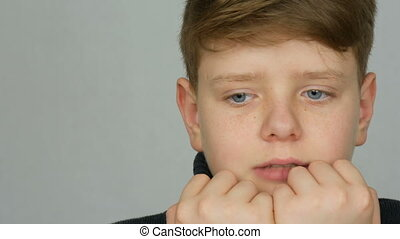 Portrait of a teenager boy who bites his nails and fingers...