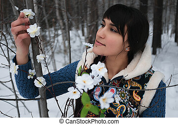 Portrait of a tender girl in the winter under an apple tree