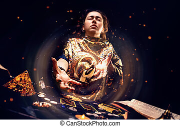 Portrait of a tense witch conjuring a magic energy ball with her hands. The concept of astrology, magic and esotericism