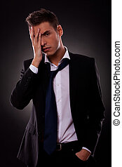 tensed young businessman with hand on the face