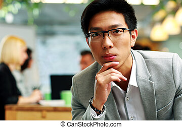 Portrait of a thoughtful asian man sitting in office, with his colleagues in background