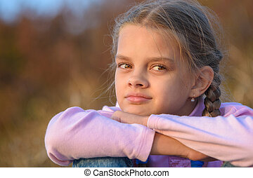 Portrait of a thoughtful beautiful ten-year-old girl at sunset