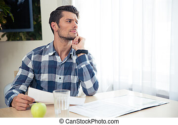 Portrait of a thoughtful man checking bills