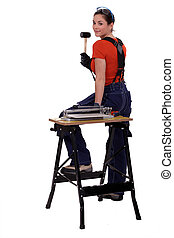 Portrait of a tile fitter standing by a workbench and holding a mallet