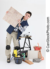 Portrait of a tile fitter with his tools and building materials