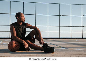 Portrait of a tired african basketball player resting after game