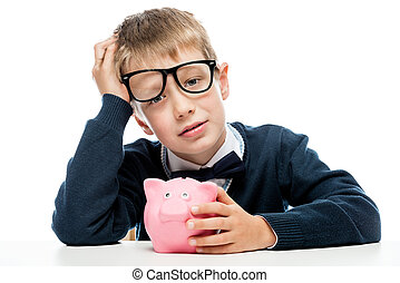 portrait of a tired boy in glasses with a piggy bank pink on...