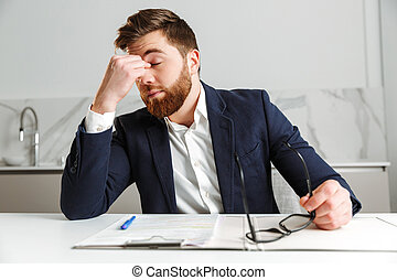 Portrait of a tired young businessman dressed in suit