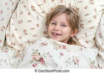 Portrait of a toothless girl in bed
