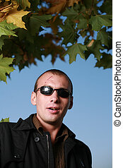 Portrait of a tough man in black sunglasses, with scars on his face.
