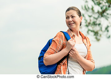 portrait of a tourist with a backpack on the nature in a hike