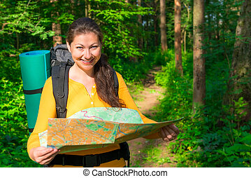 portrait of a tourist with a map in the forest