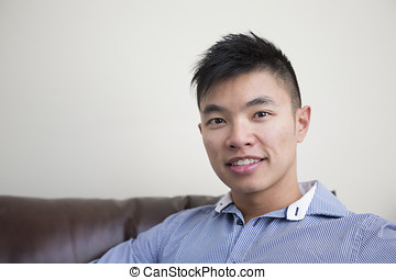 Chinese man relaxing at home. - Portrait of a trendy Asian ...