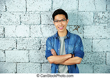 Portrait of a trendy smiling asian man leaning on brick wall
