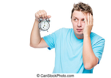 Portrait of a troubled sleepy man with an alarm clock on white background