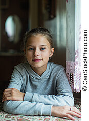 Portrait of a twelve-year-old cute girl sitting at the table.