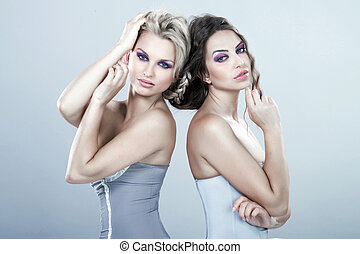 Portrait of a two beautiful sexy young women. Connected to the h