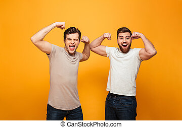 Portrait of a two cheerful young men showing biceps