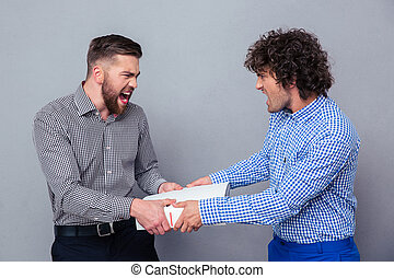 Portrait of a two men fighting for folder
