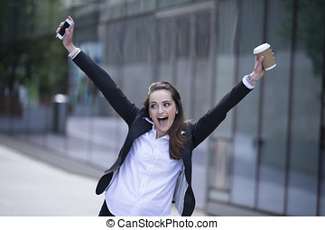 Portrait of a very happy business woman celebrating good...