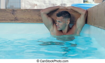 Portrait of a wet sexy muscular guy with blue eyes swimming in a pool , slow motion