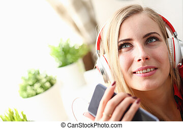 Portrait of a woman at home in headphones