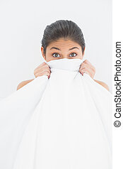 Portrait of a woman covering face with bedsheet