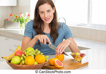 Portrait of a woman cutting fruits in kitchen