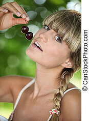 portrait of a woman eating cherries