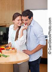 Portrait of a woman feeding her husband