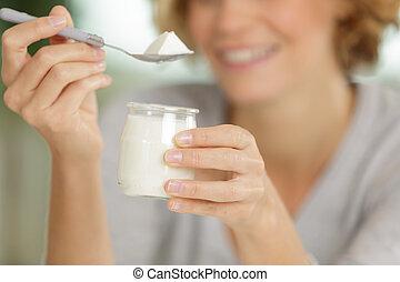 portrait of a woman having a yogurt