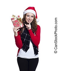 Portrait of a woman holding a Christmas present with finger on her lips over white background, Model: Brittany Beaudoin