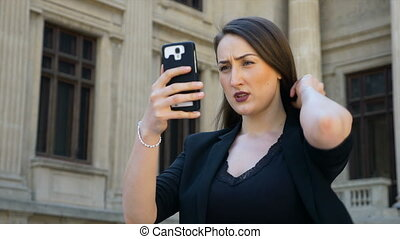 Portrait of a woman holding a smartphone and taking selfies...