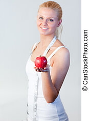 Portrait of a woman holding an apple with focus on apple