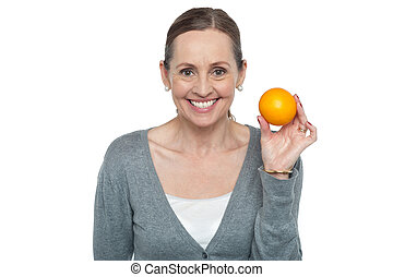 Portrait of a woman holding up an orange