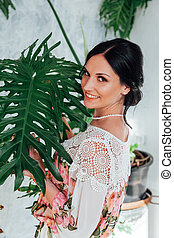 Portrait of a woman in a dress with flowers in a white room with homeplants